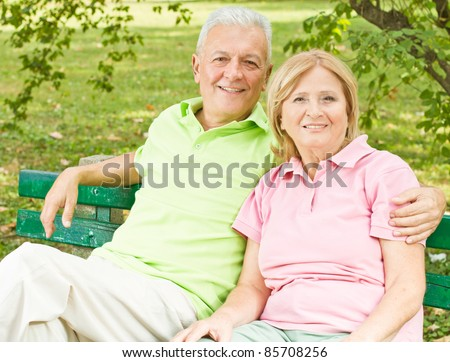 Happy elderly couple relaxed on the park bench. - stock photo