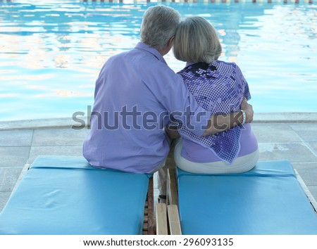 Happy Elderly couple resting near pool water together at vacation - stock photo