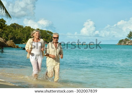 Happy elderly couple running  on a beach