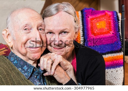 Happy elderly couple sitting in living-room with faces together - stock photo