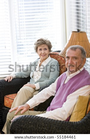 Happy elderly couple sitting on living room couch, focus on woman - stock photo