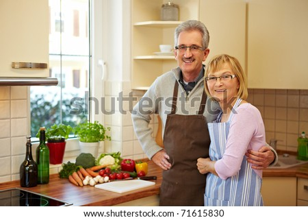 Happy elderly couple standing smiling in a new kitchen - stock photo