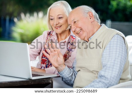 Happy elderly couple video chatting on laptop while sitting at nursing home porch - stock photo