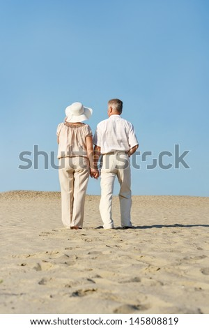 happy elderly couple walking barefoot on the sand in the summer - stock photo