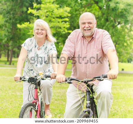 Happy elderly couple with bike in the park. - stock photo