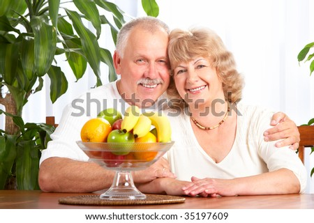 Happy elderly couple with fresh fruits.