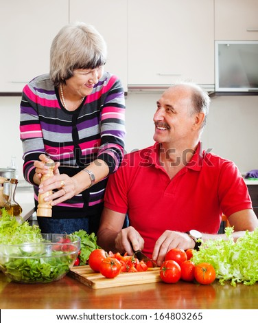 happy elderly couple with fresh vegetables and greens in home kitchen