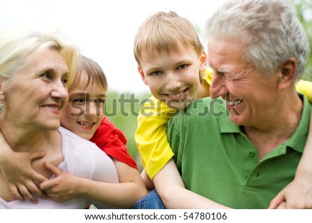 happy elderly couple with their grandchildren in the summer - stock photo
