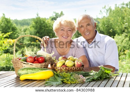 Happy elderly couple with this year's rich harvest - stock photo