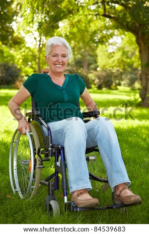 Happy elderly disabled woman in a wheelchair in a park - stock photo