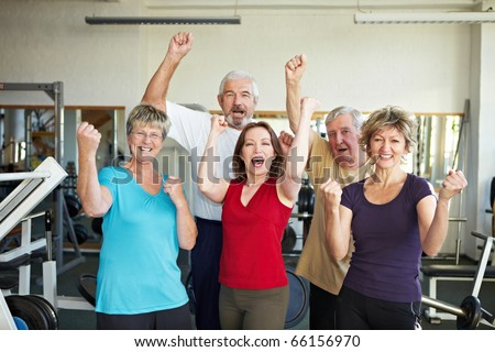 Happy elderly group in a gym cheering - stock photo