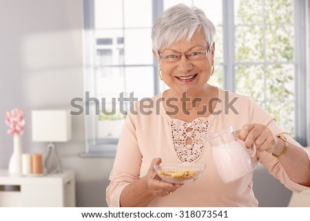 Happy elderly lady preparing breakfast cereal, pouring milk, looking at camera.