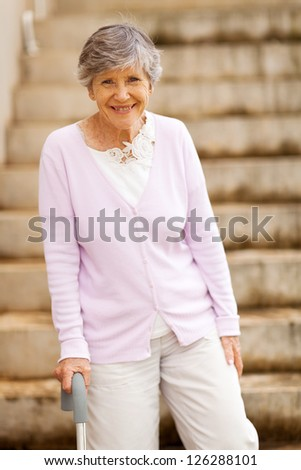 happy elderly lady standing by stairway with cane - stock photo
