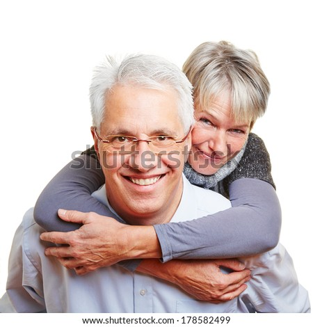 Happy elderly man carrying smiling senior woman piggyback - stock photo