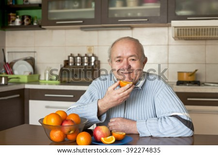 happy elderly man eating fruit