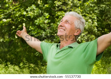 happy elderly man in a summer park - stock photo