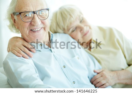 Happy elderly man looking at camera with his wife on background - stock photo