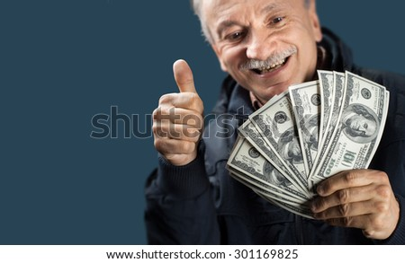 Happy elderly man showing fan of money and sign OK with fingers on blue background with copy-space. Focus on money and the hand, face blurred