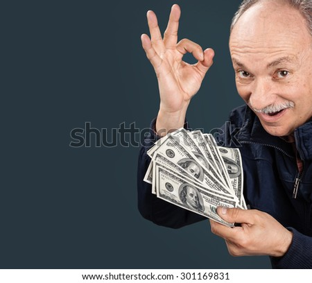 Happy elderly man showing fan of money and sign OK with fingers on dark blue background with copy-space