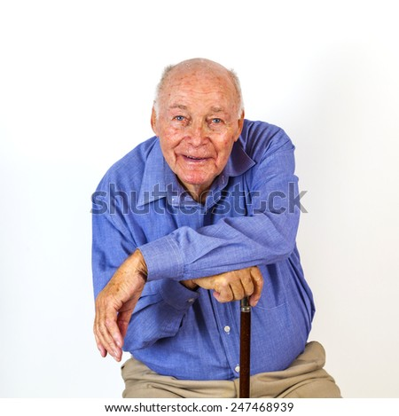 happy elderly man sitting in front of a white background - stock photo
