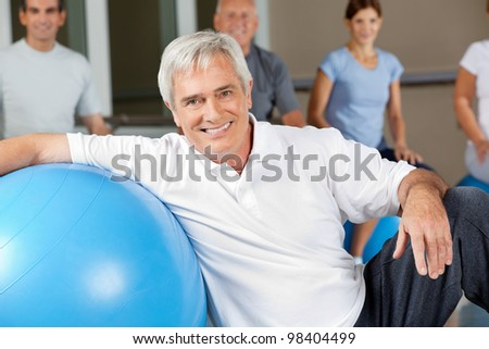 Happy elderly man sitting next to gym ball in fitness center
