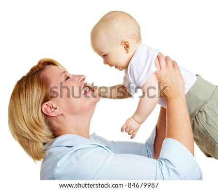 Happy elderly mother lifting a smiling baby - stock photo