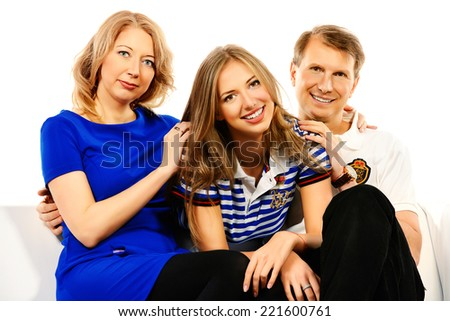 Happy elderly parents sitting on a sofa with their adult daughter. Isolated over white.