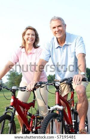 Happy elderly senior couple biking in park - stock photo