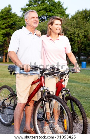Happy elderly senior couple cycling in park.