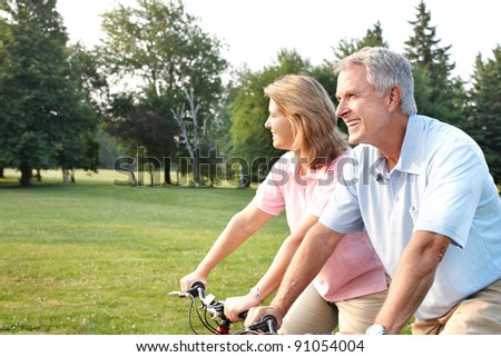 Happy elderly senior couple cycling in park. - stock photo