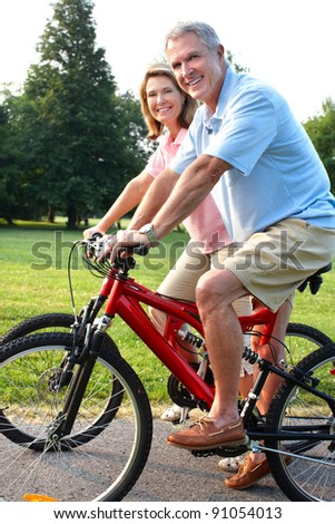 Happy elderly senior couple cycling in park. - stock photo