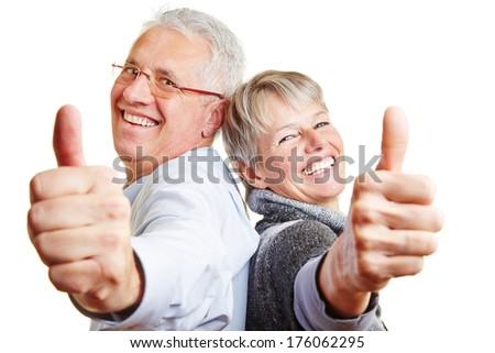 Happy elderly senior couple holding their thumbs up - stock photo