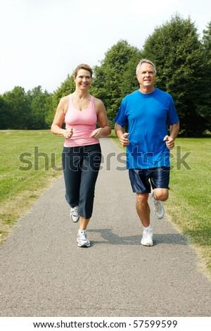 Happy elderly senior couple jogging in park - stock photo
