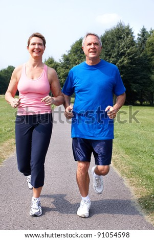 Happy elderly senior couple jogging in park. - stock photo