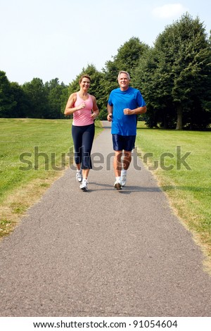 Happy elderly senior couple jogging in park. - stock photo