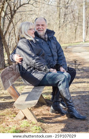 Happy Elderly Senior Couple Relaxing in the nature. Old people sitting on the bench portrait outdoor winter autumn season. - stock photo