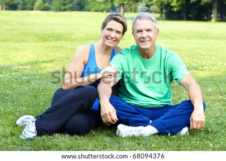 Happy elderly senior couple relaxing in the park - stock photo