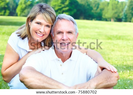 Happy elderly senior couple relaxing in the park - stock photo