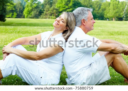 Happy elderly senior couple relaxing in the park