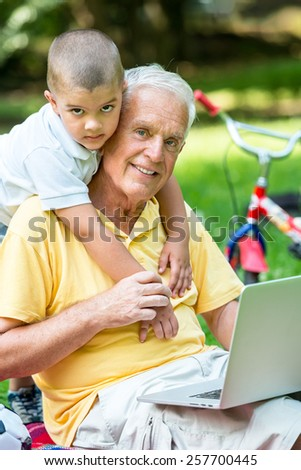happy elderly senior grandfather and child in park using laptop computer
