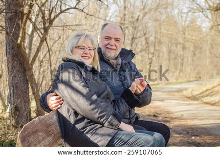 Happy Elderly Senior Romantic Couple Relaxing in the nature. Old people sitting on the bench portrait outdoor winter autumn season. - stock photo