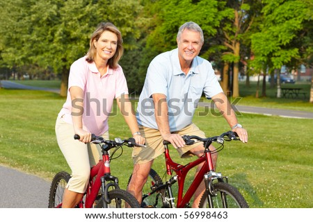 Happy elderly seniors couple biking in park - stock photo