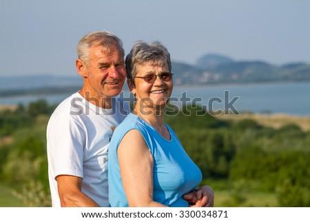 Happy elderly seniors couple in outdoors - stock photo