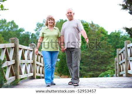 Happy elderly seniors couple in park - stock photo