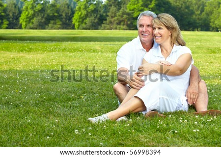happy  elderly seniors couple in park - stock photo