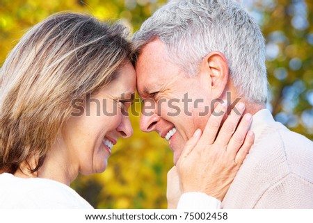 Happy elderly seniors couple in park. Love. - stock photo