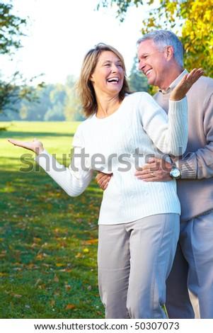 happy  elderly seniors couple in the forest - stock photo