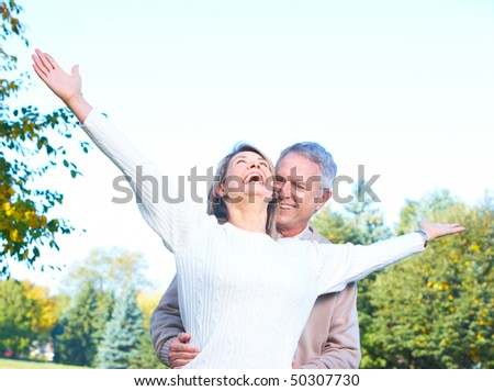 happy  elderly seniors couple in the forest - stock photo