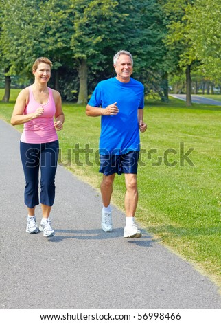 Happy elderly seniors couple jogging in park - stock photo
