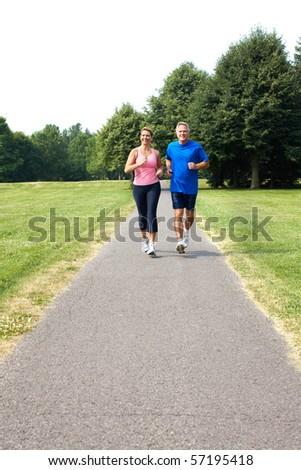 Happy elderly seniors couple jogging in park - stock photo